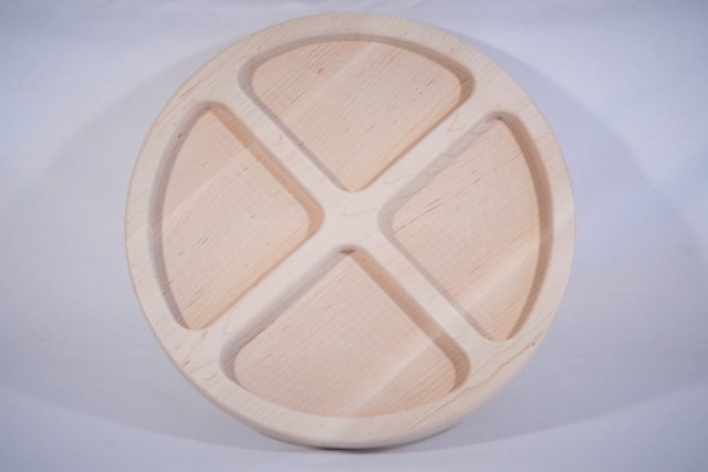 A piece of maple with pockets milled by a CNC machine